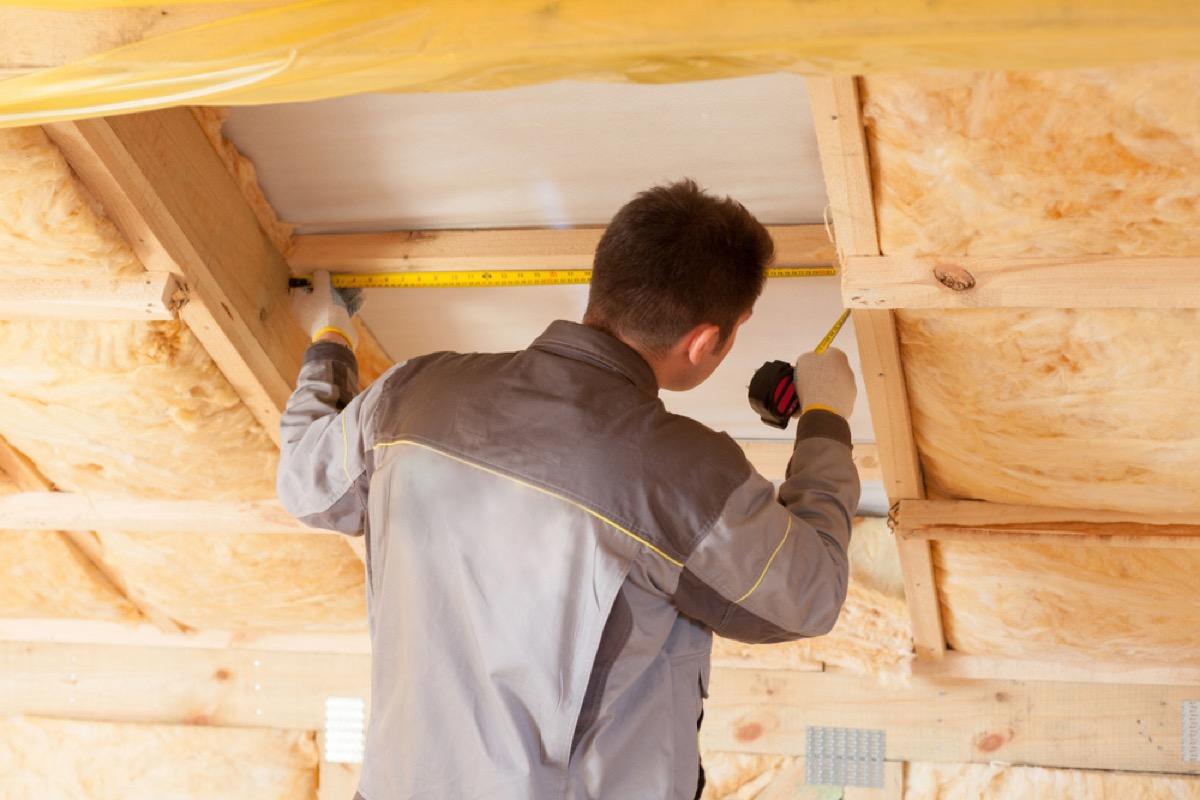 man installs insulation in attic