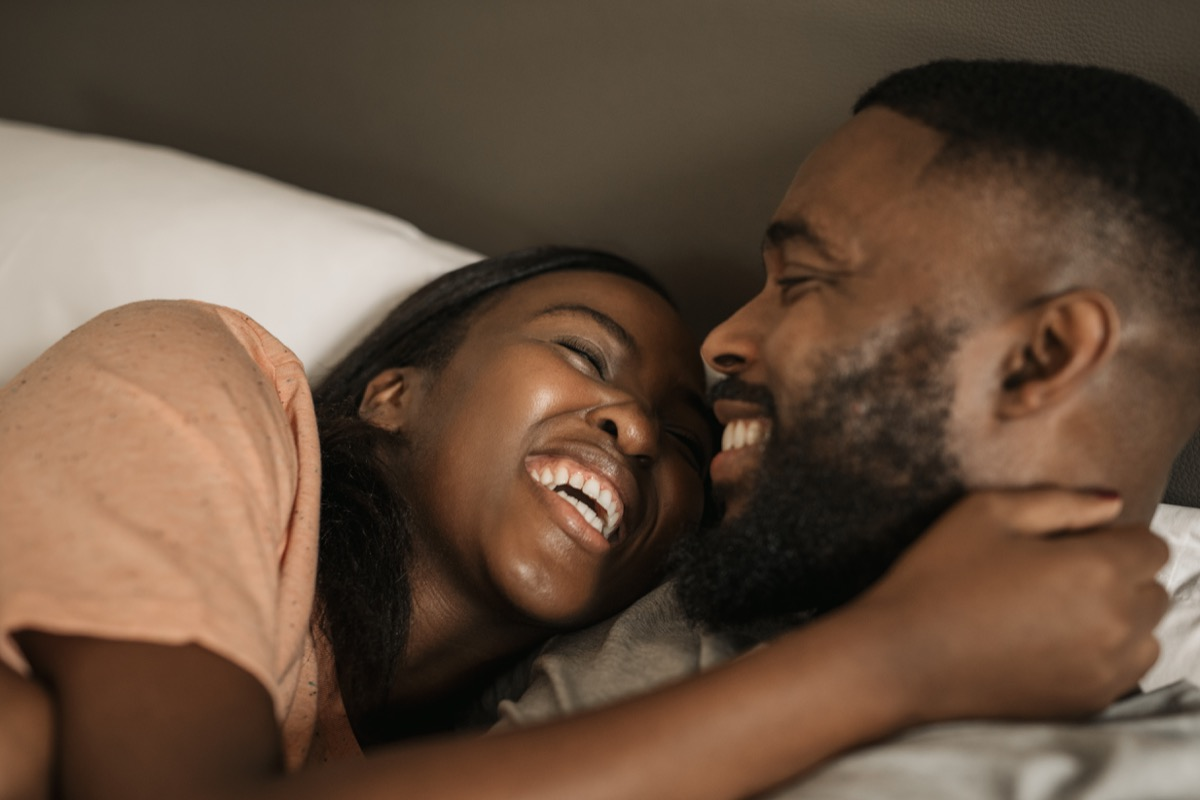 Happy black couple cuddling in bed