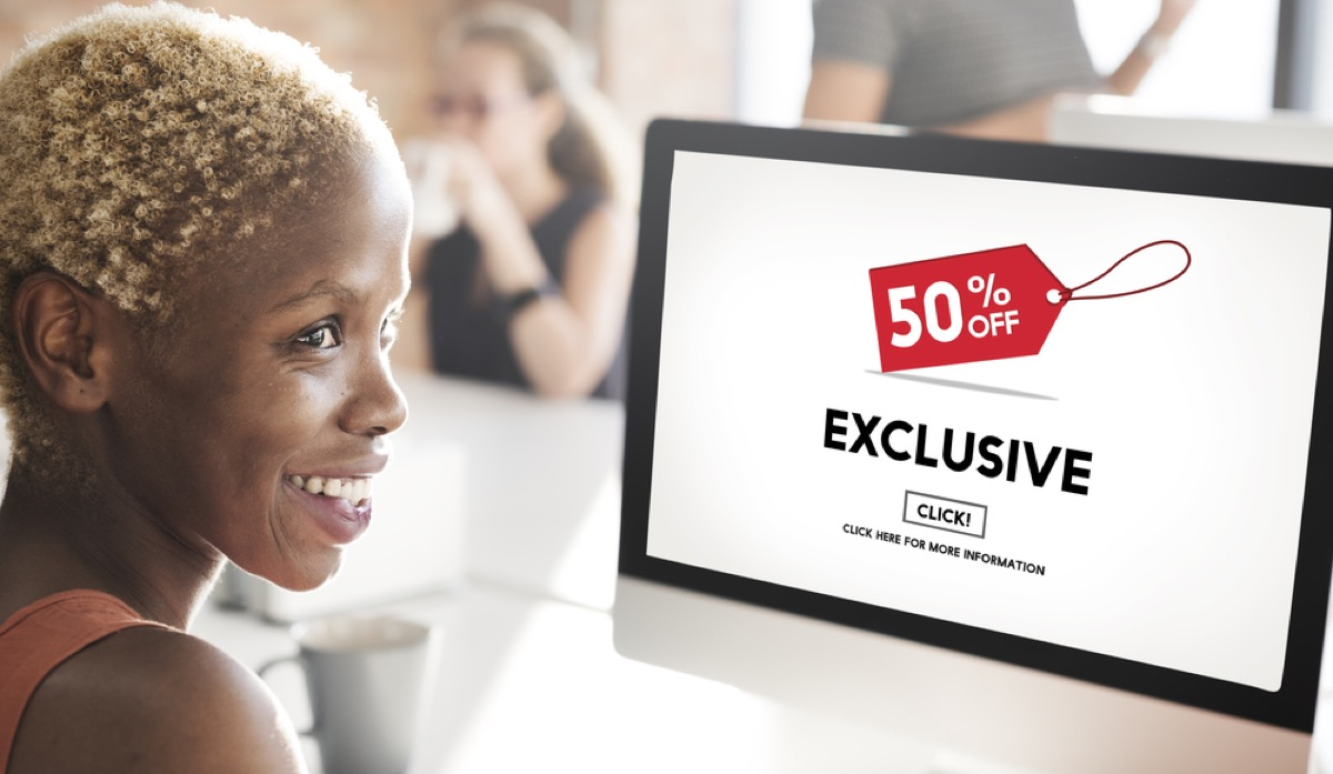black woman online shops on computer, which shows exclusive deal