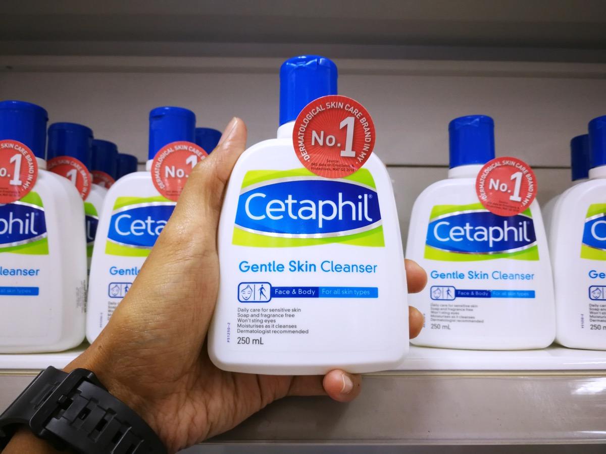 man holding a cetaphil bottle off the shelf