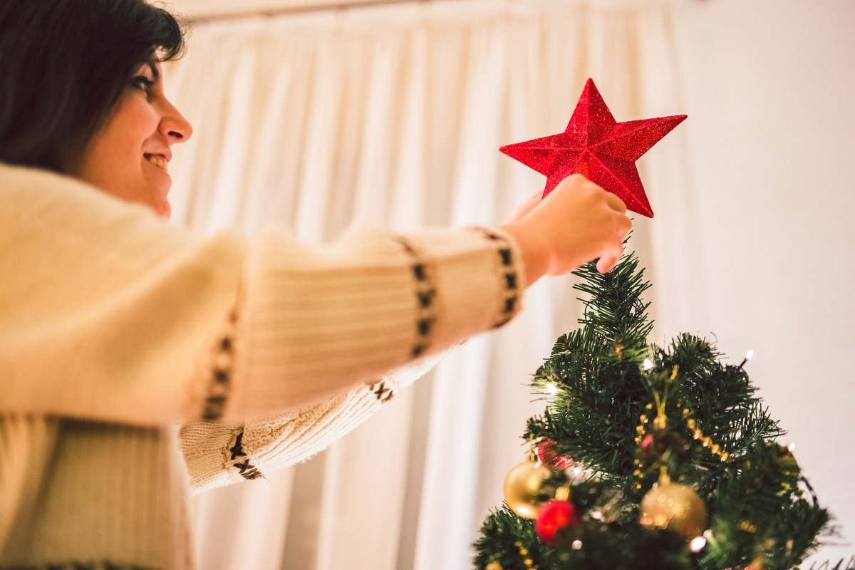 woman placing tree topper on tree