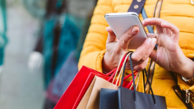 closeup of shopper in yellow coat with bags and phone in hand