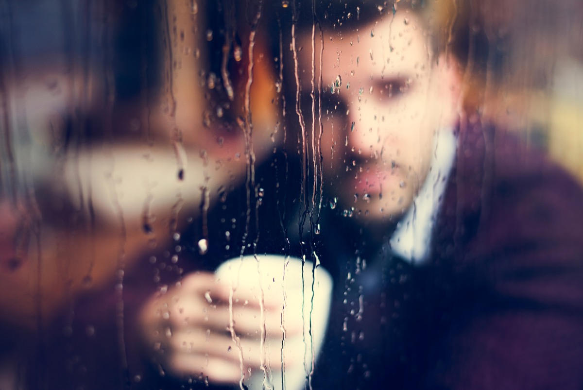 contemplative man holding a cup of coffee looking out a rainy window {stereotypes}