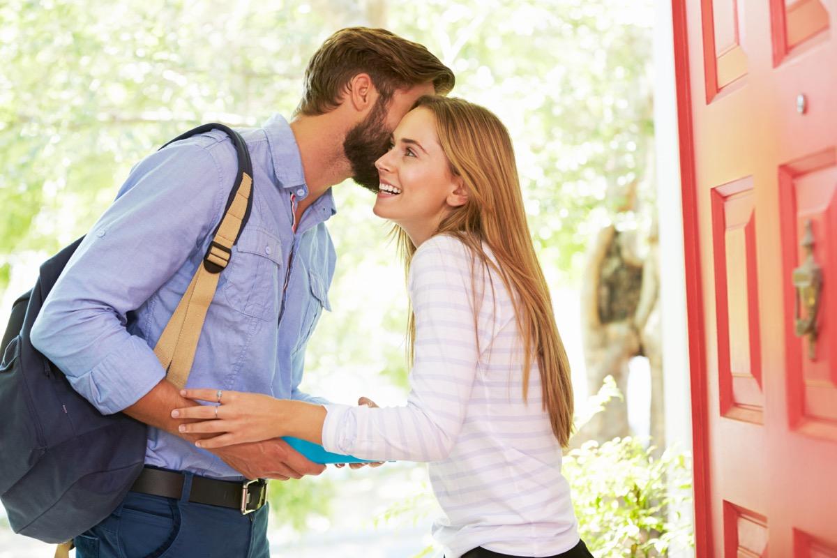 Couple kissing goodbye in the doorway before work