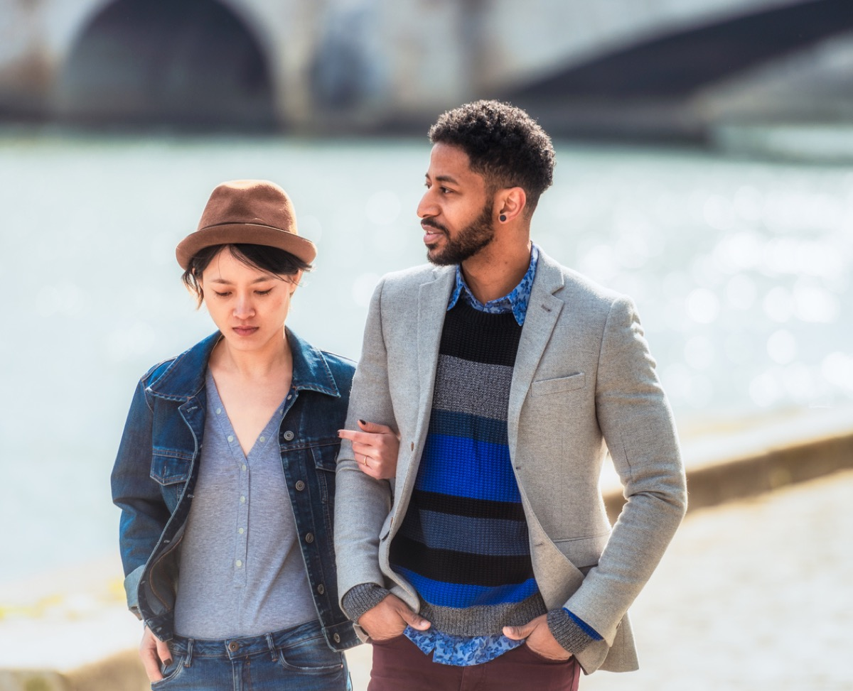 A young couple in discussion together as they walk by the Seine.