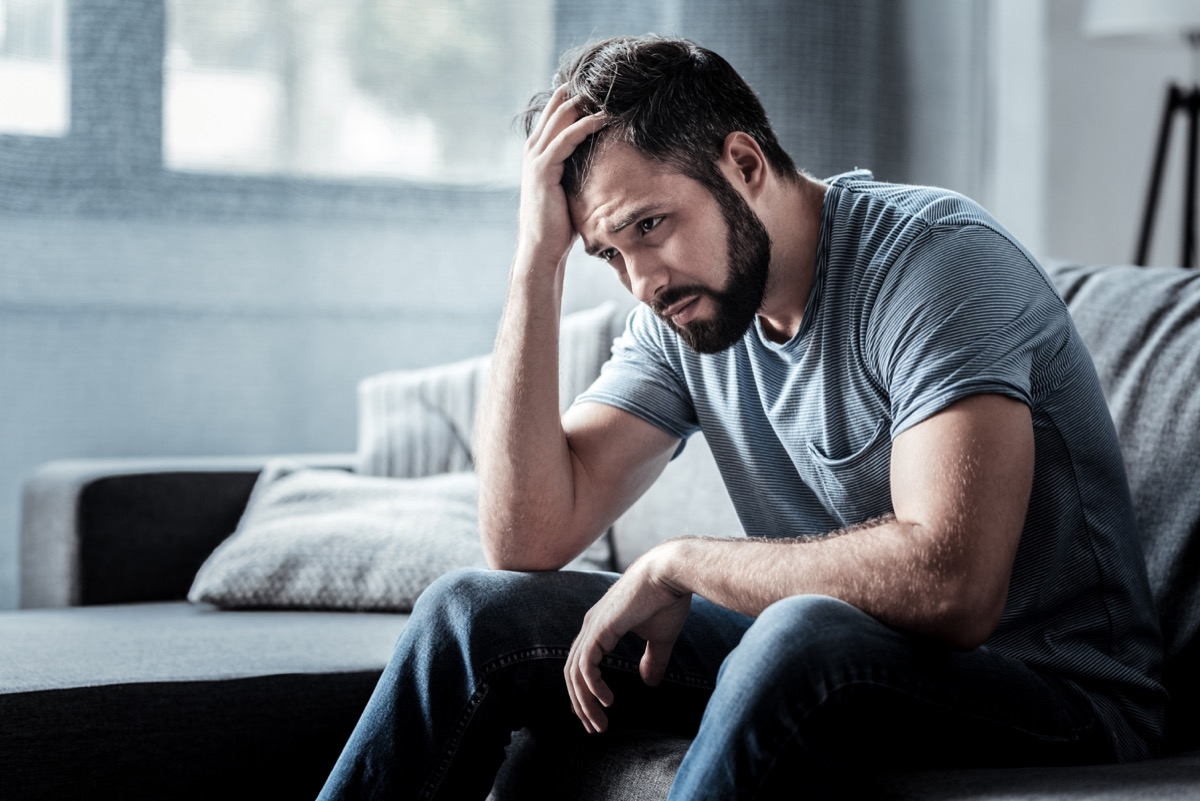 Depressed sad man with head in his hands