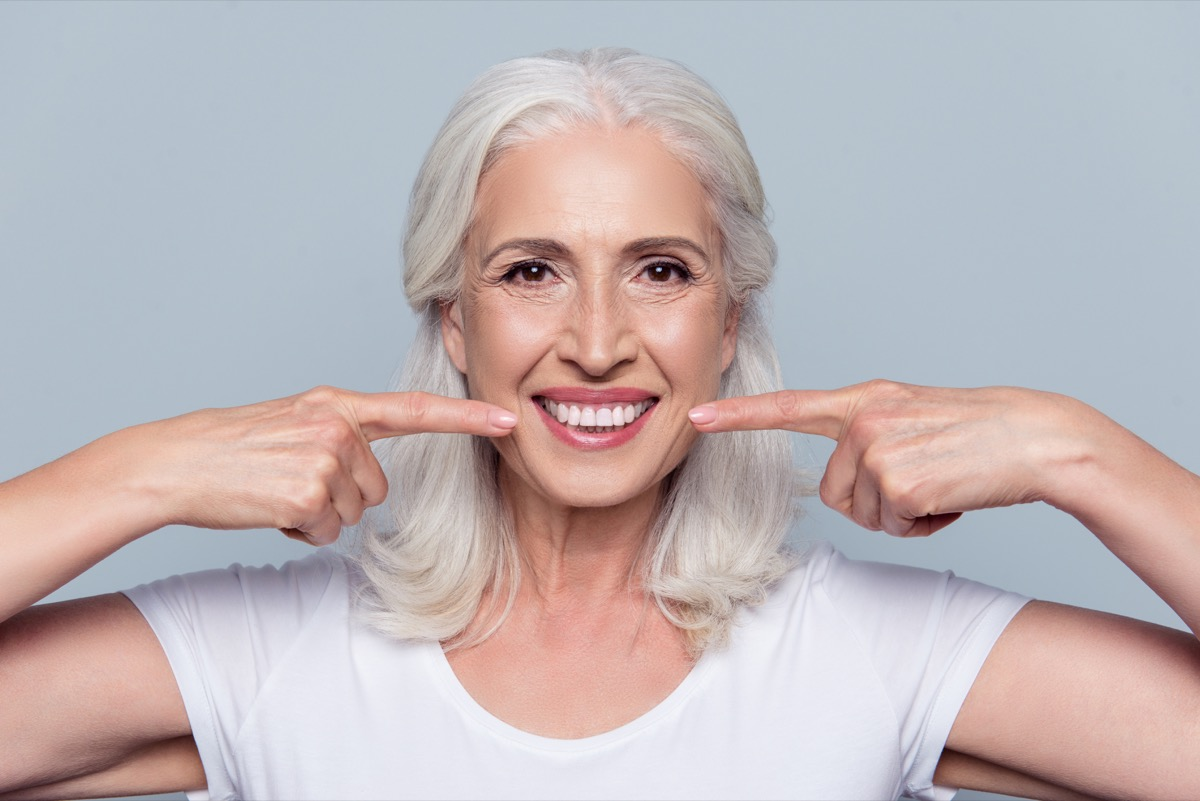 older woman giving a fake smile