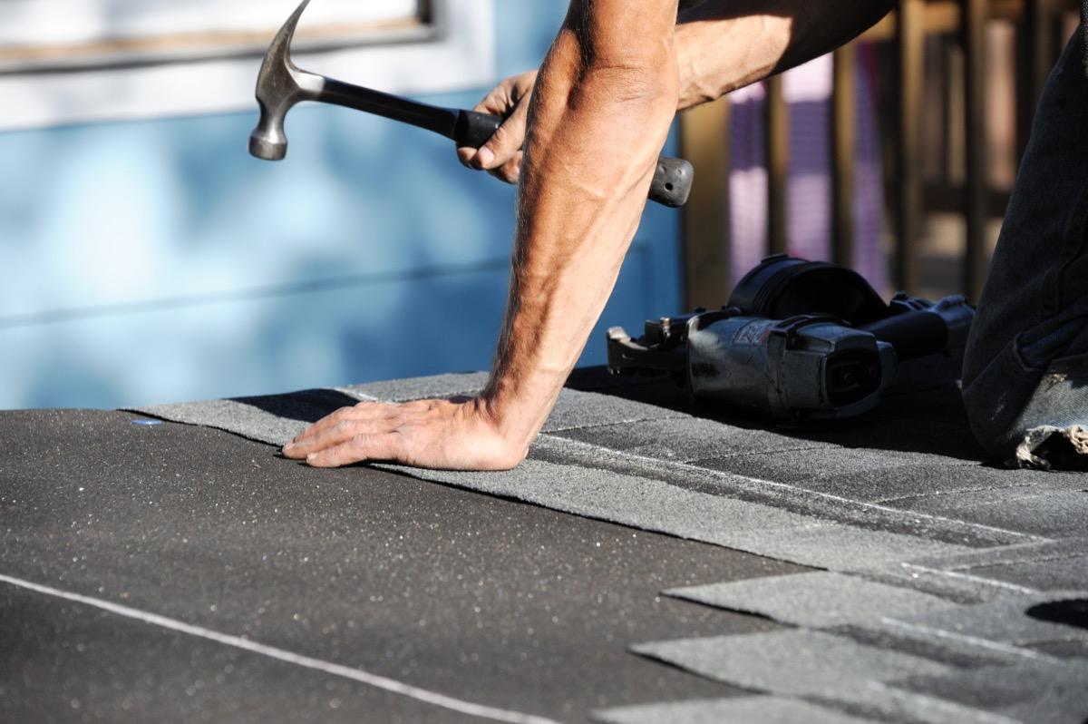 white man hammering shingles onto roof