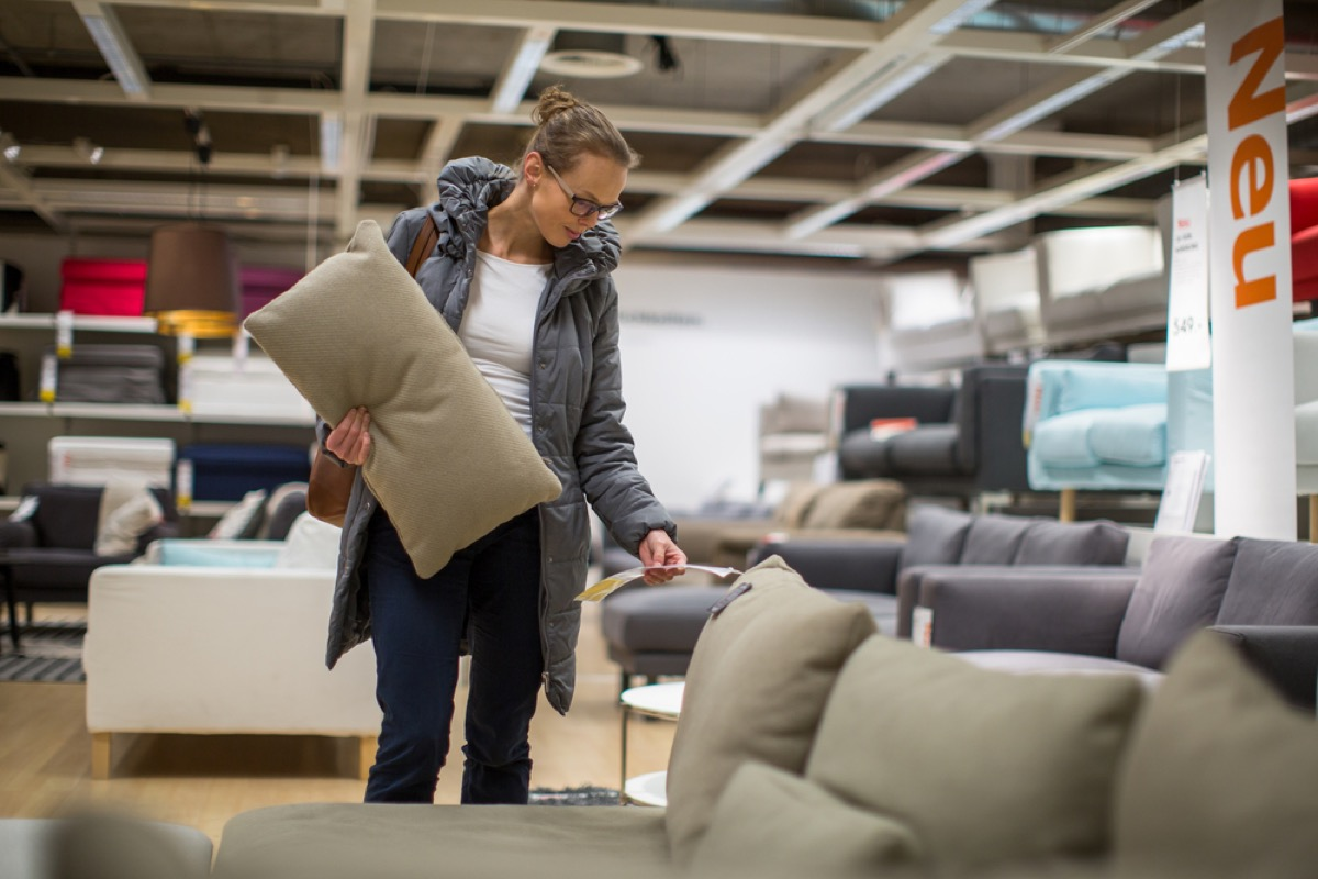woman checks price of couch while furniture shopping
