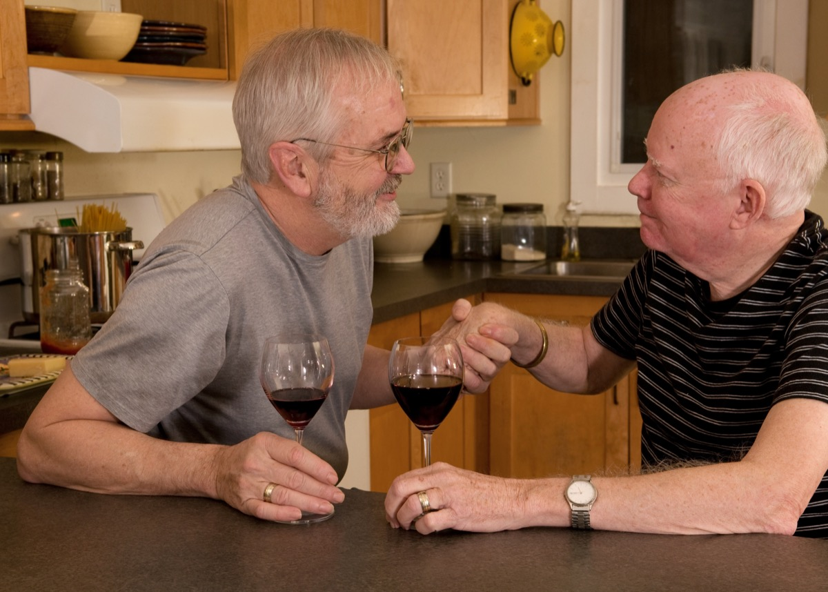 Gay couple having a serious conversation over wine