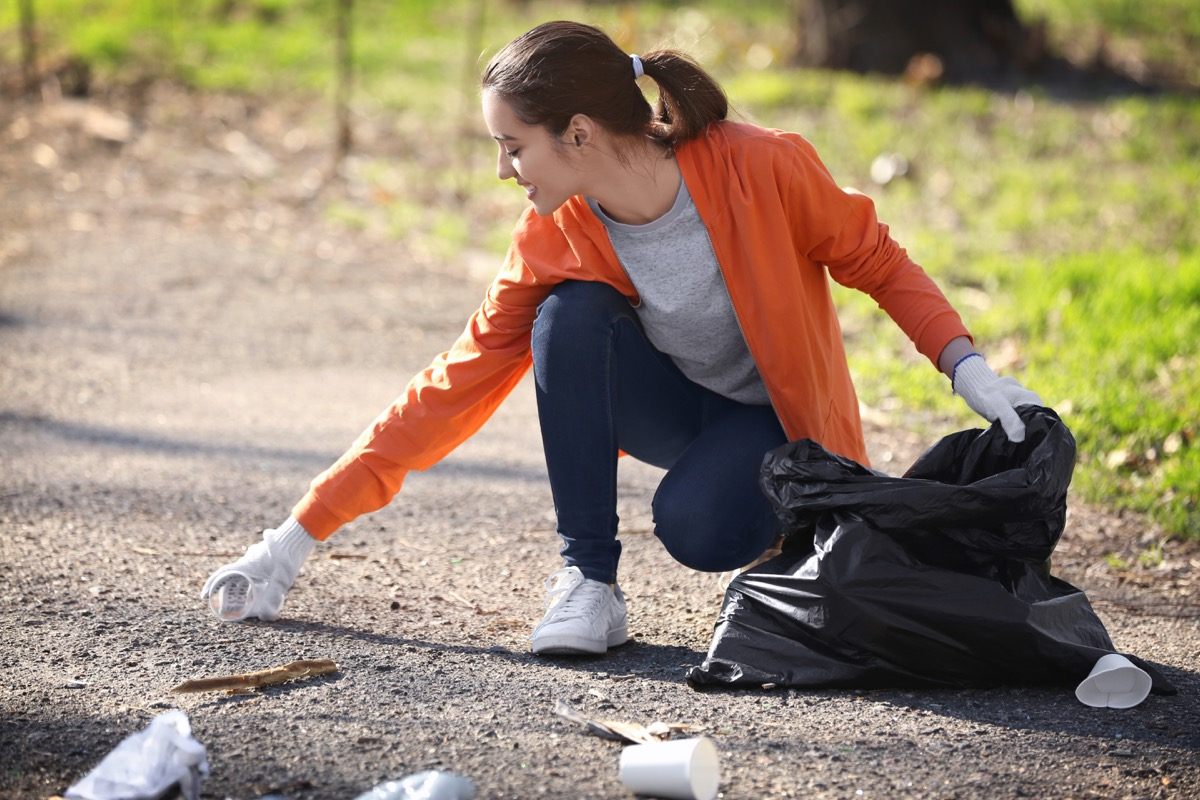 girl picking up litter in park small acts of kindness