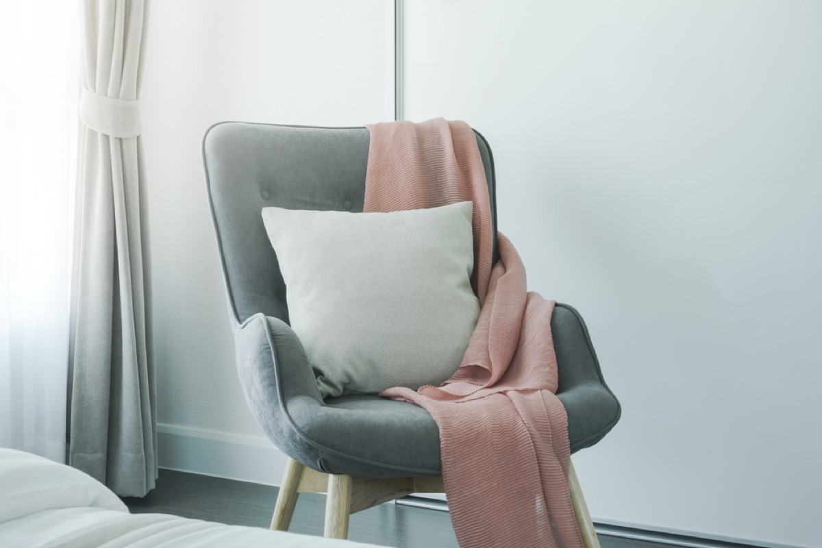 gray upholstered chair with pink blanket and white pillow