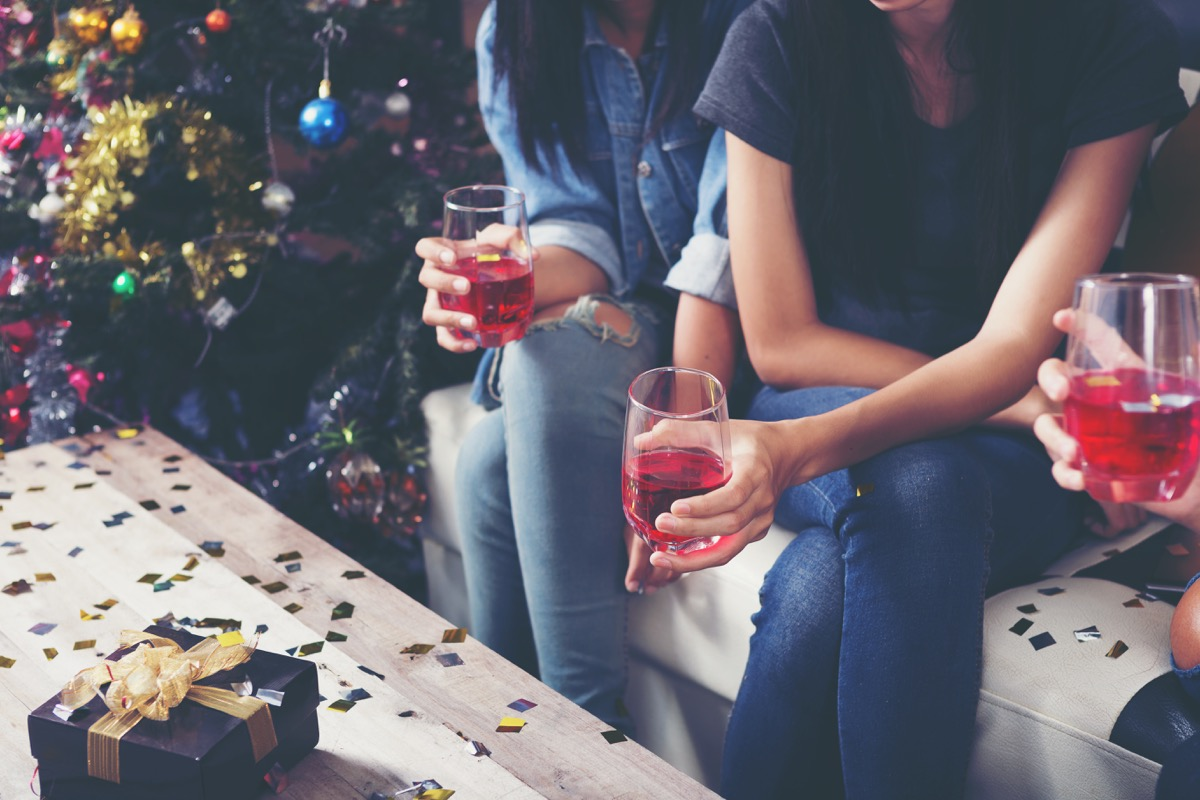 group of adults holding their drinks at a christmas party