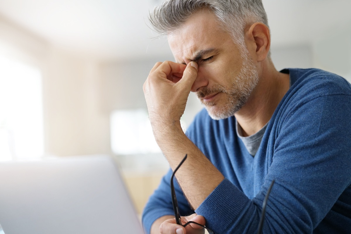 Stressed man with a pressure headache between eyes