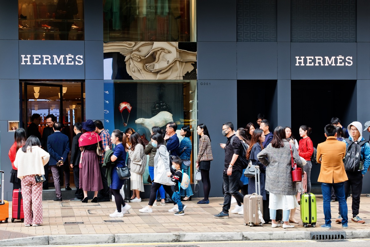 Tsim Sha Tsui, Hong Kong - 08 December, 2018 : People walk past the HERMES Shop in Canton Road, Hong Kong. People queuing outside and waiting to enter the store.