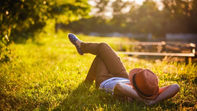 hipster laying in a grass lawn at sunset - self love