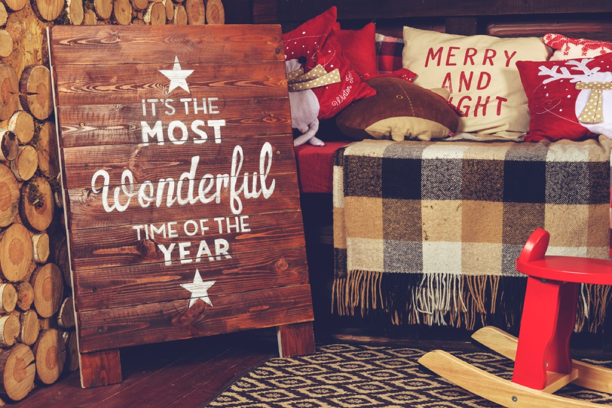 """bench with plaid blanket and wooden sign in front of it reading """"it's the most wonderful time of the year"""""""