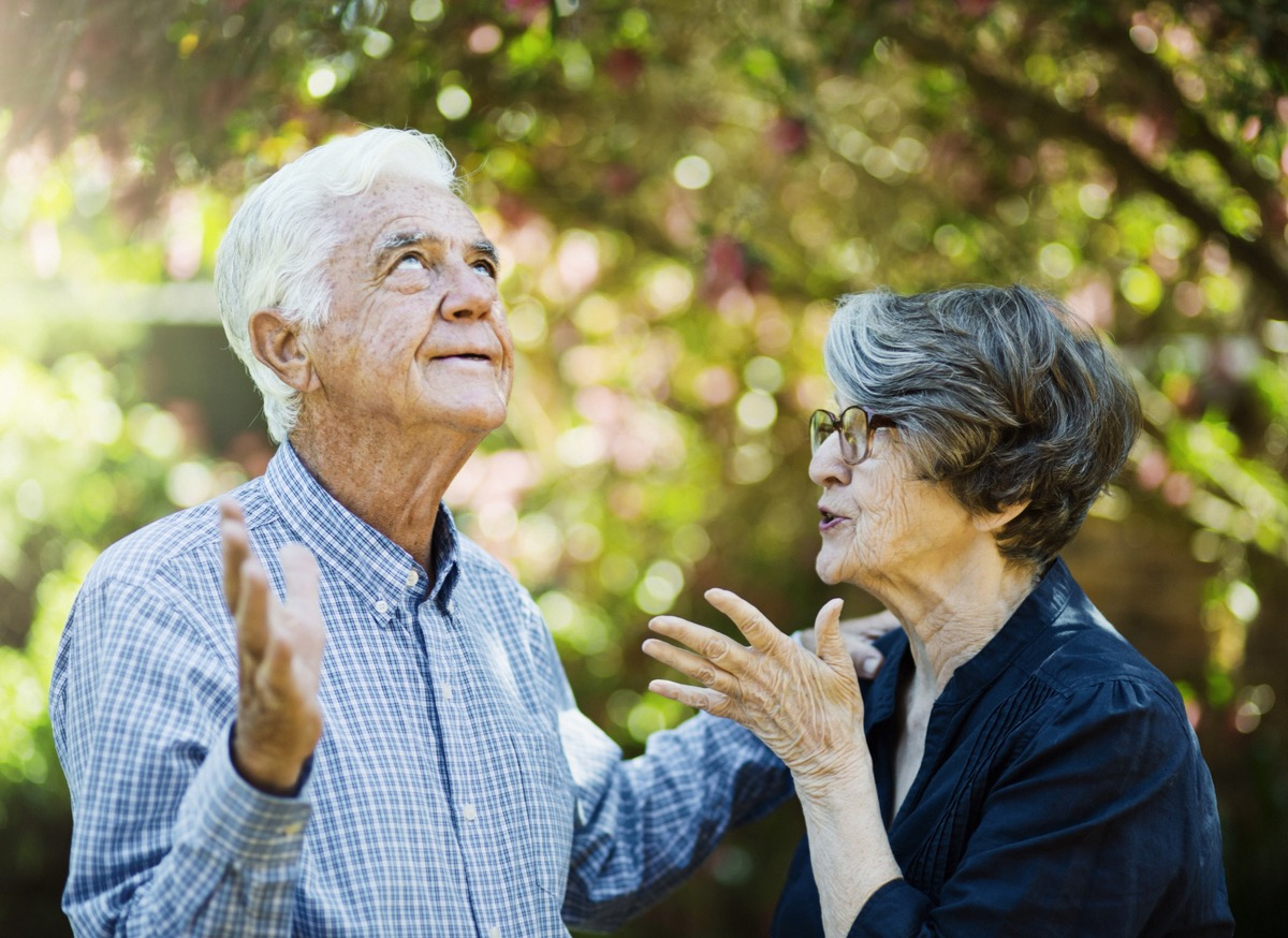 A senior man rolls his eyes, frustrated, as his partner gestures at him angrily.
