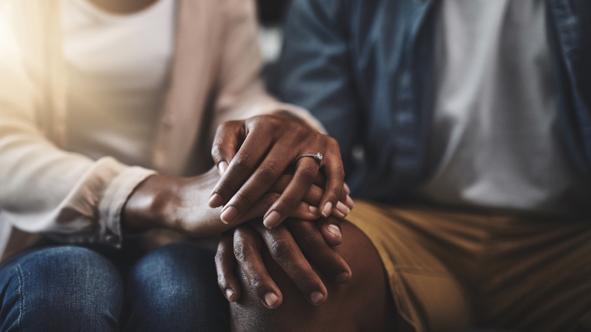 close up of black married couple holding hands