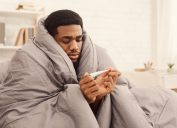 sick black man under a blanket looking at a thermometer
