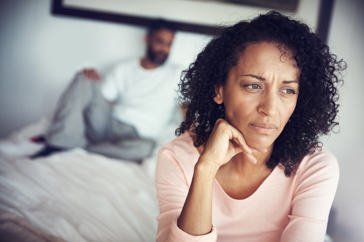 woman looks upset with husband lying on bed behind her