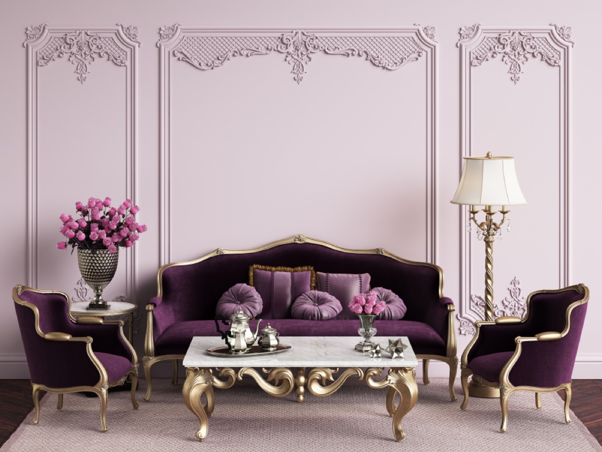 purple living room with purple velvet couch and gold table