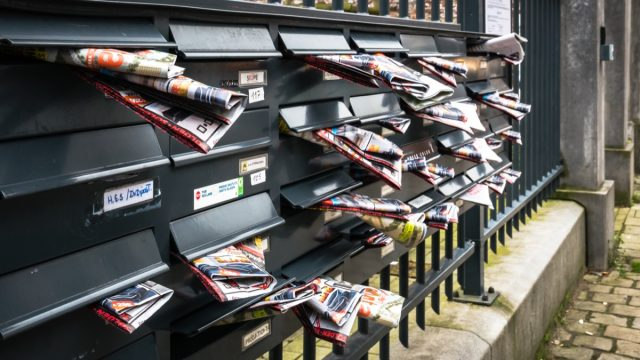 junk mail stuffed in the mailboxes of an apartment complex in brussels