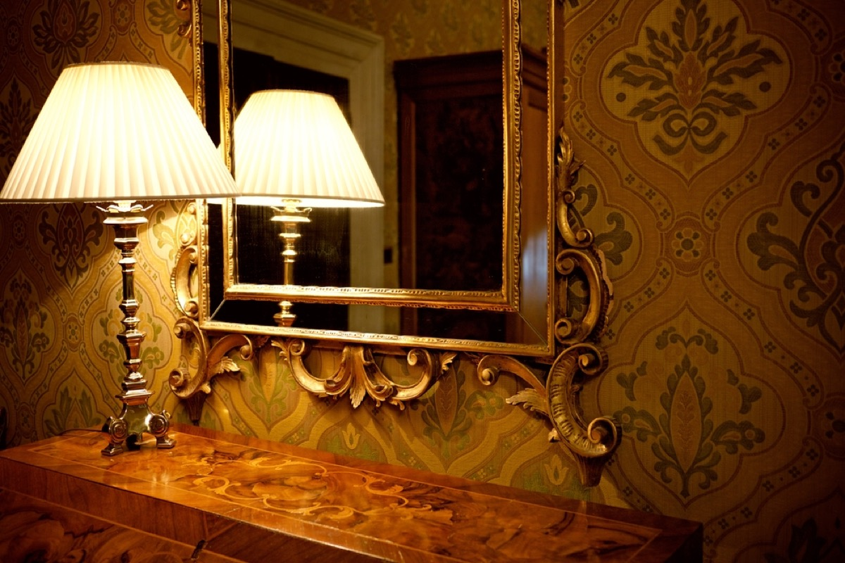 old fashioned lamp in front of gilded mirror on credenza