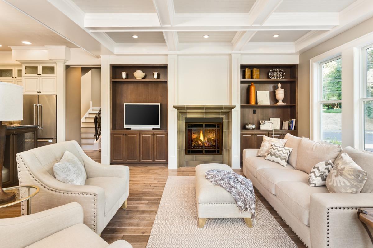 white couches and chairs facing each other in living room with fireplace