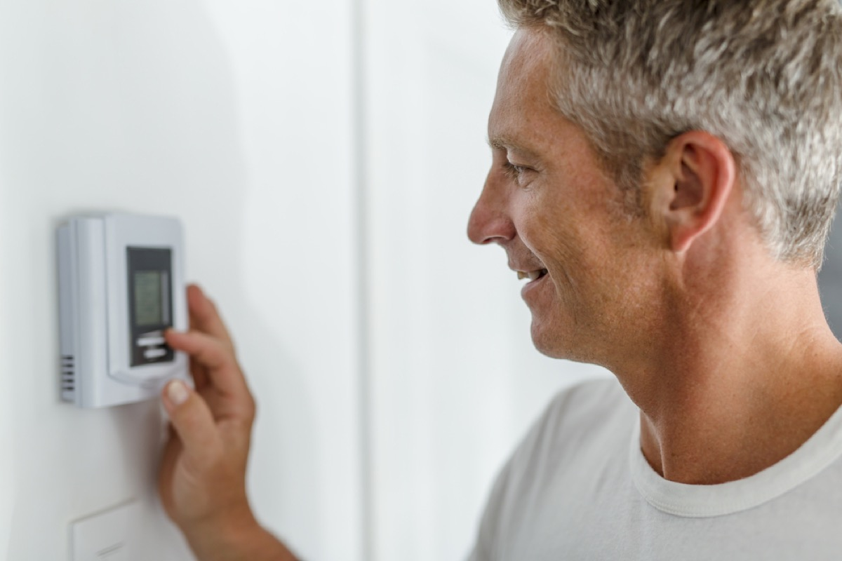 white man with gray hair adjusts thermostat while smiling