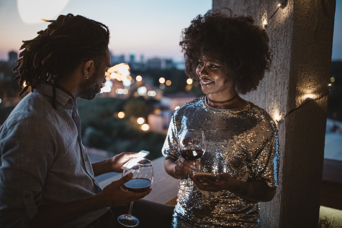 young couple having date night on balcony. Drinking wine, talking and surfing the net. Well dressed.