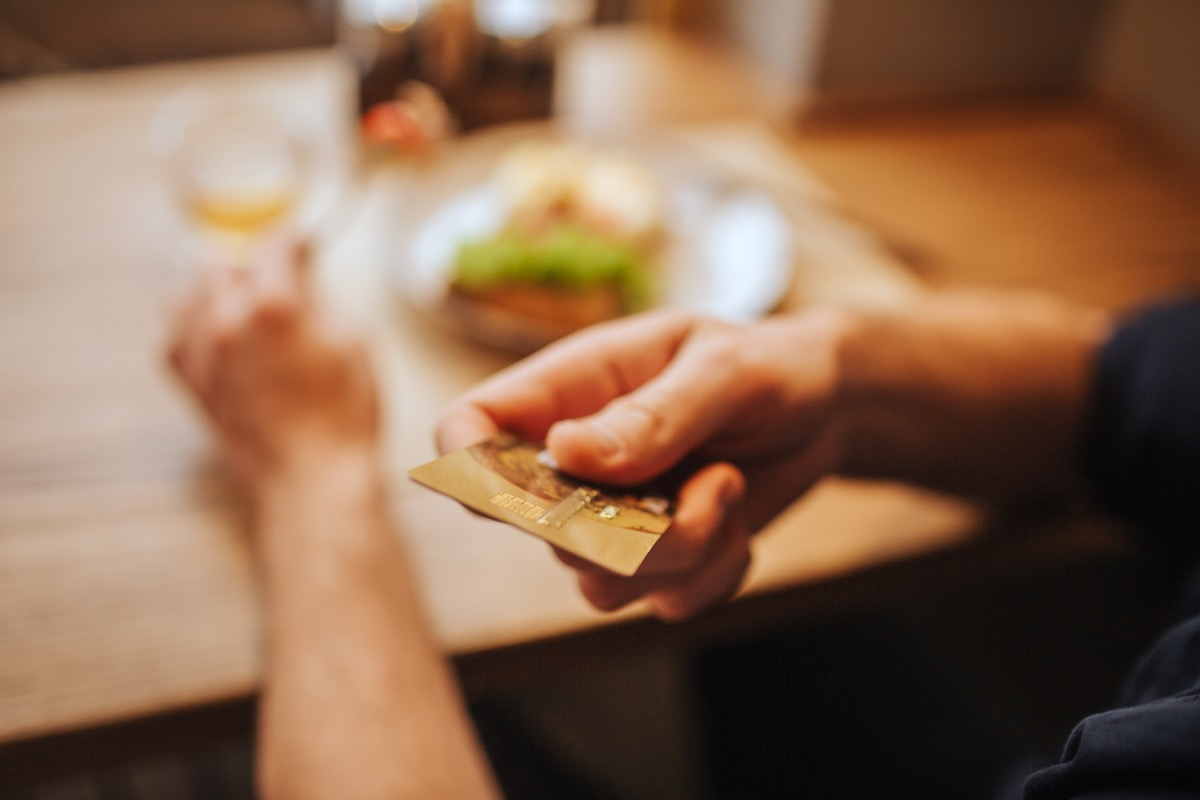close up of a mail hand hanging server his card to pay the bill at a restaurant