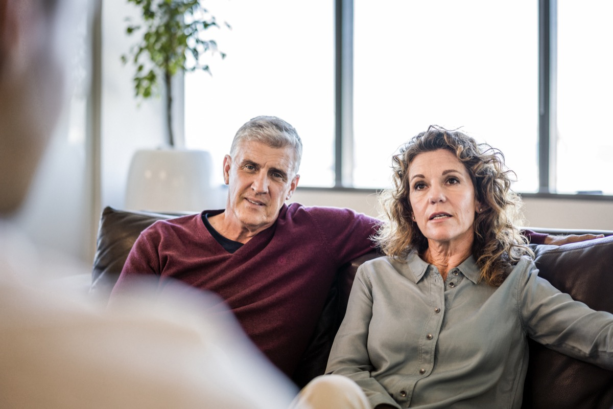 older couple talking to a man out of the screen while sitting on a couch