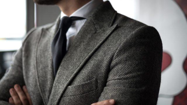 close up shot of a man wearing a tweed peak lapel sport coat - why do coats have lapels