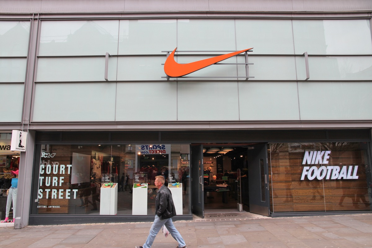 Man walks by Nike sports fashion store in Manchester, UK. Nike brand was valued at 19 billion USD in 2014.