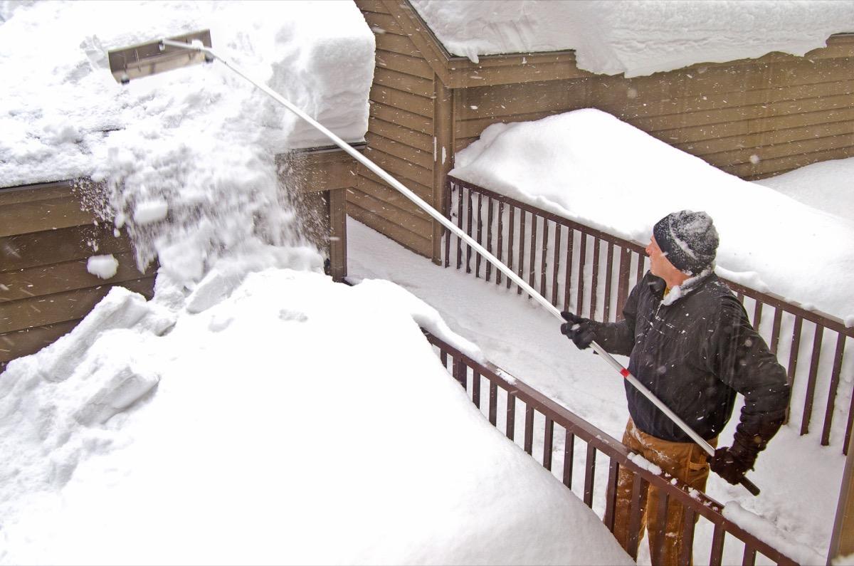 white man in winter clothing raking snow off roof