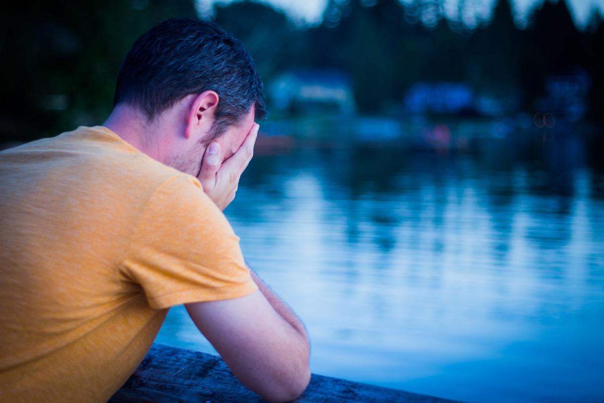 sad man looking out at lake - life choices