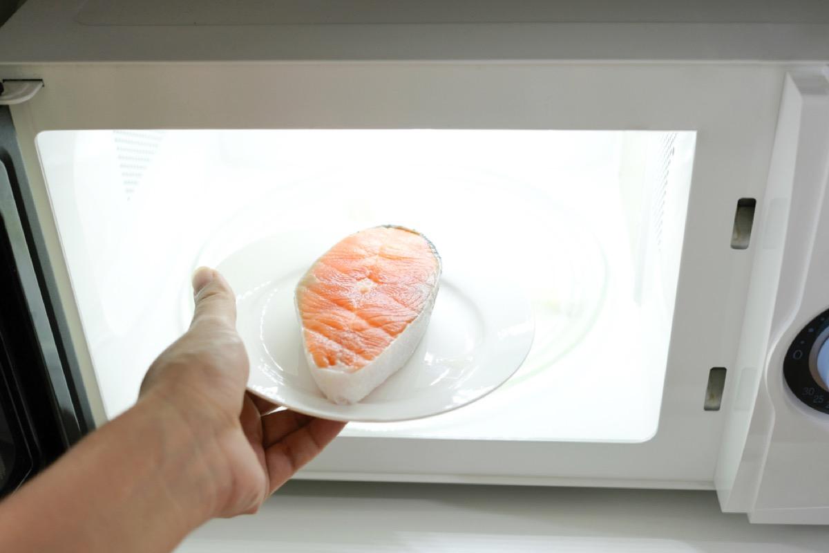 hand putting salmon filet into microwave, rude behavior