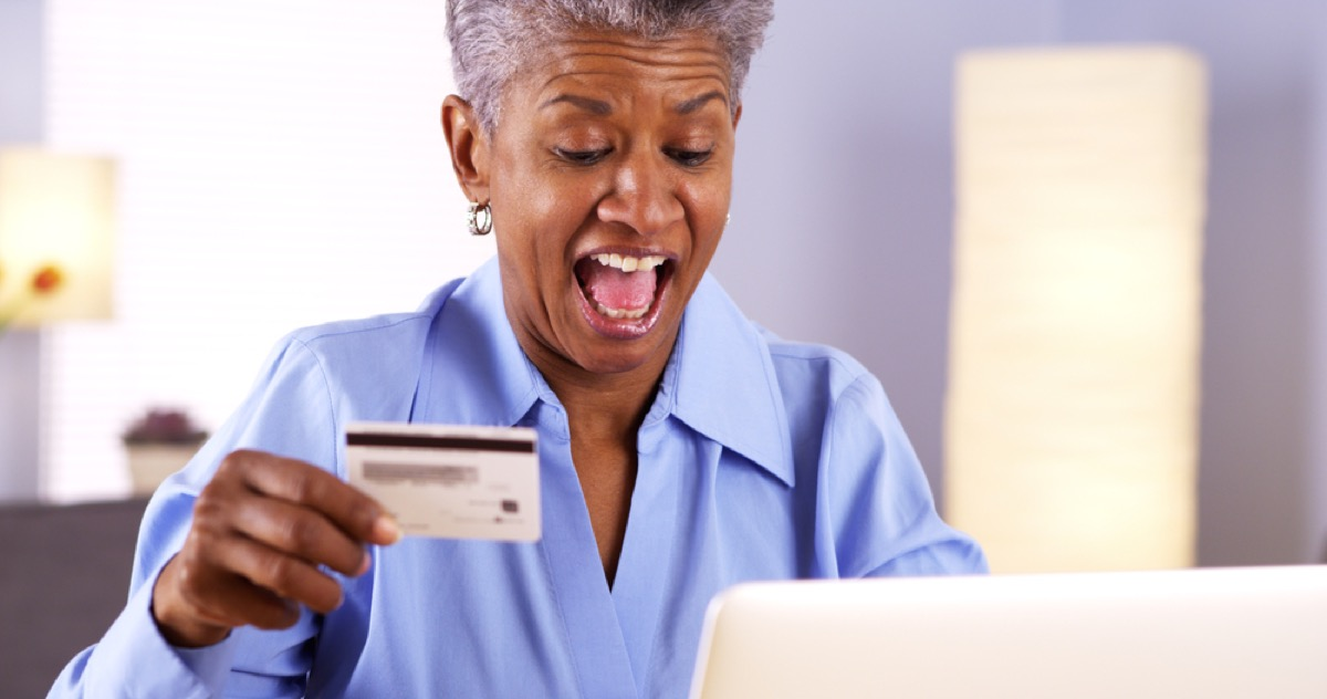 senior black woman at laptop with credit card in hand
