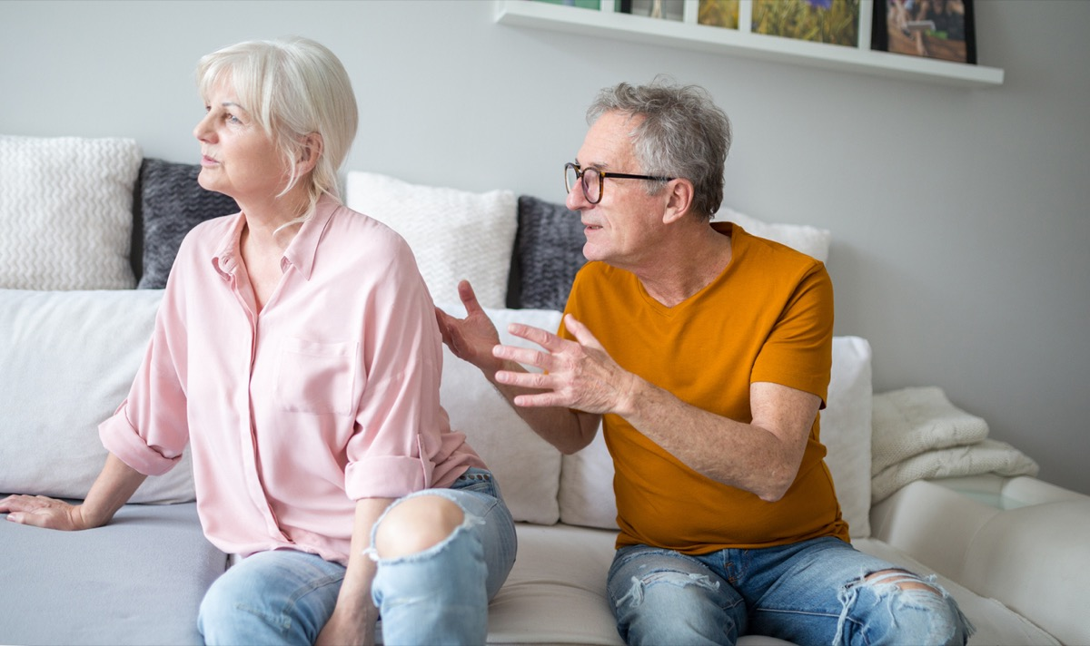 Senior man arguing with his wife who has her back turned to him as they sit on the couch