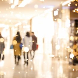 shopping mall with lights in the foreground and people in the background going holiday shopping