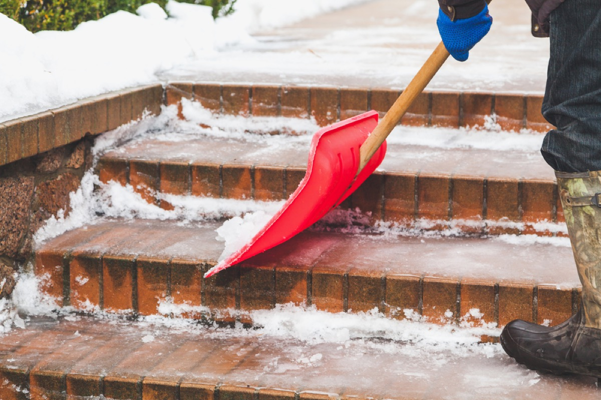 person shoveling snow on brick steps with red shovel