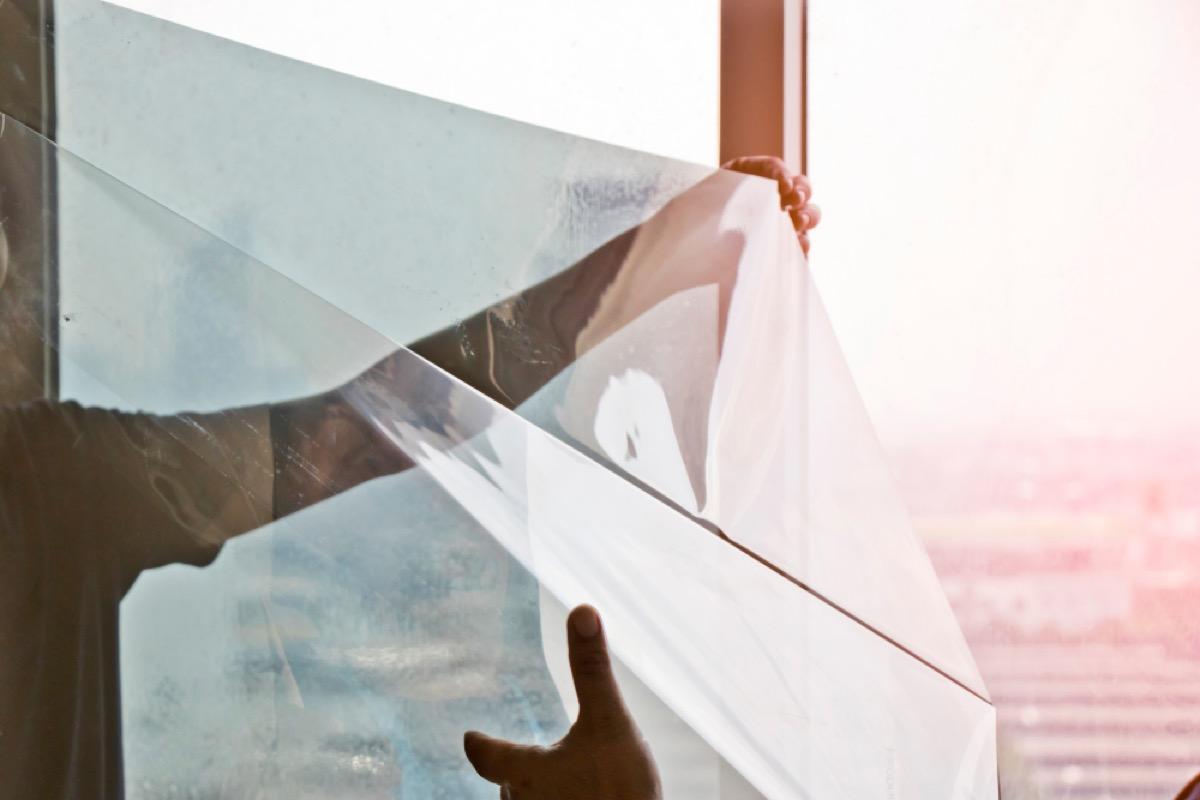 white hand applying plastic film to window