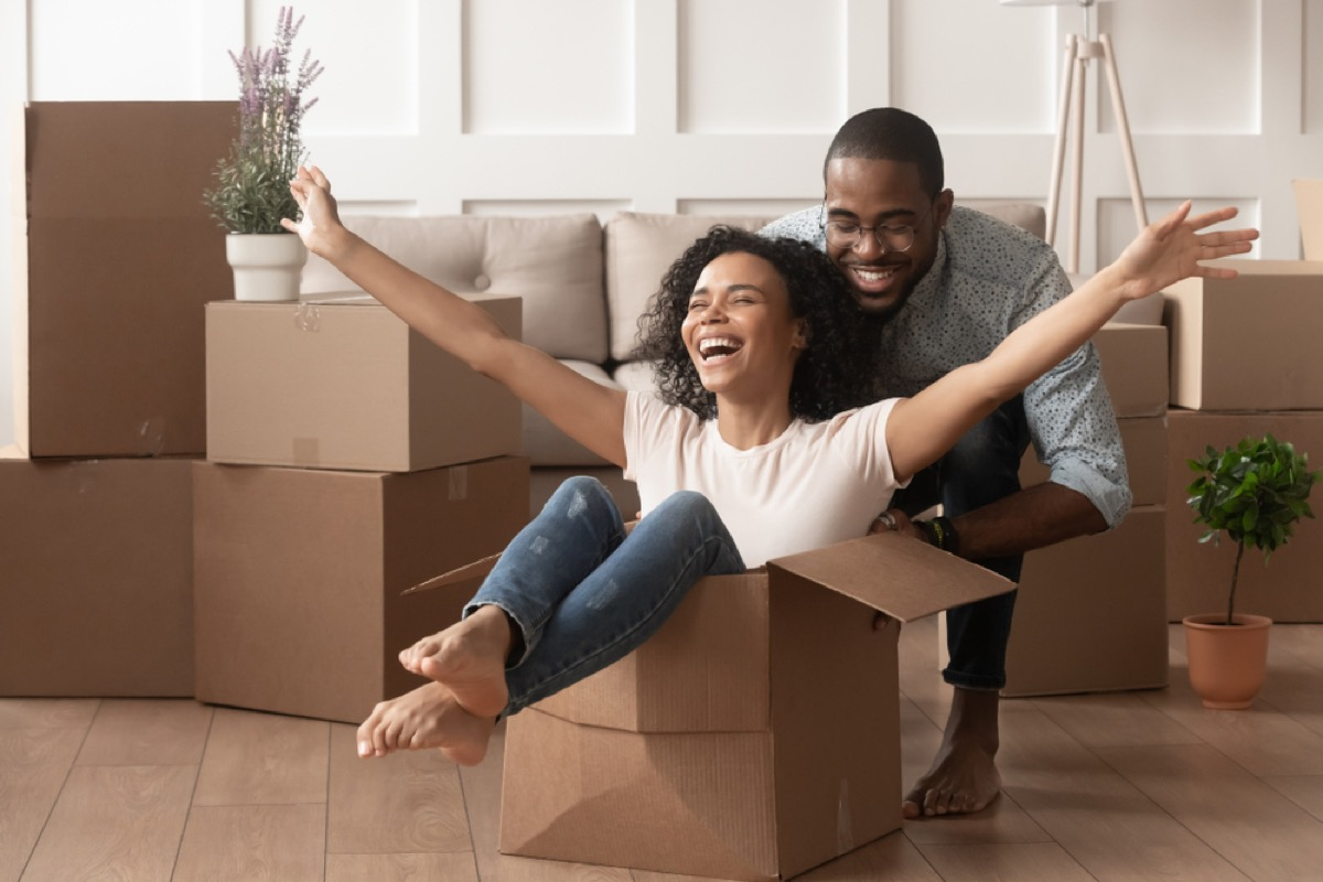 happy black woman sitting in a box with her husband behind her and other boxes