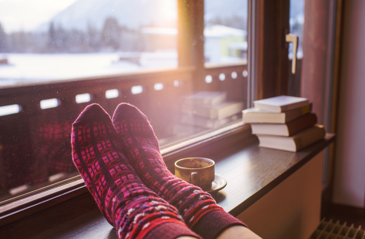 socks on a heater next to books and a cup of tea in a home in winter