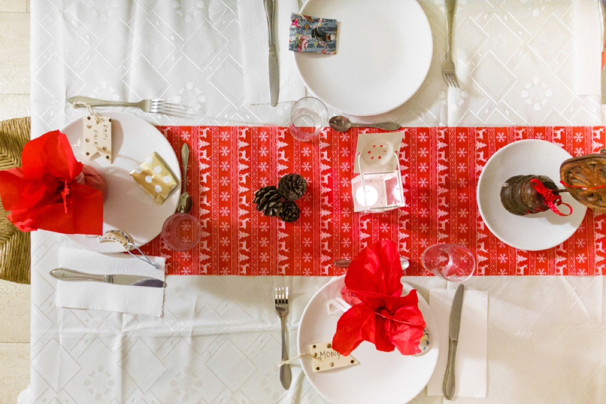dining table with white plates and red holiday runner