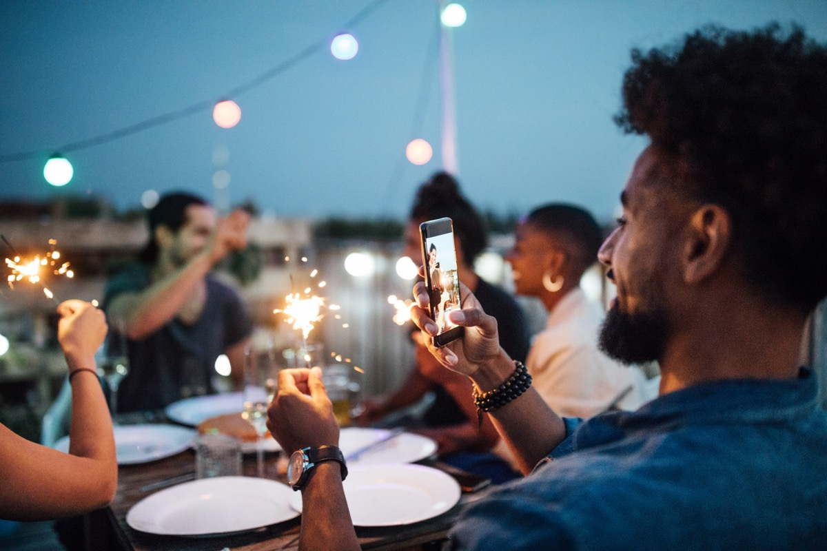 man taking a picture of sparkler at a party on his phone