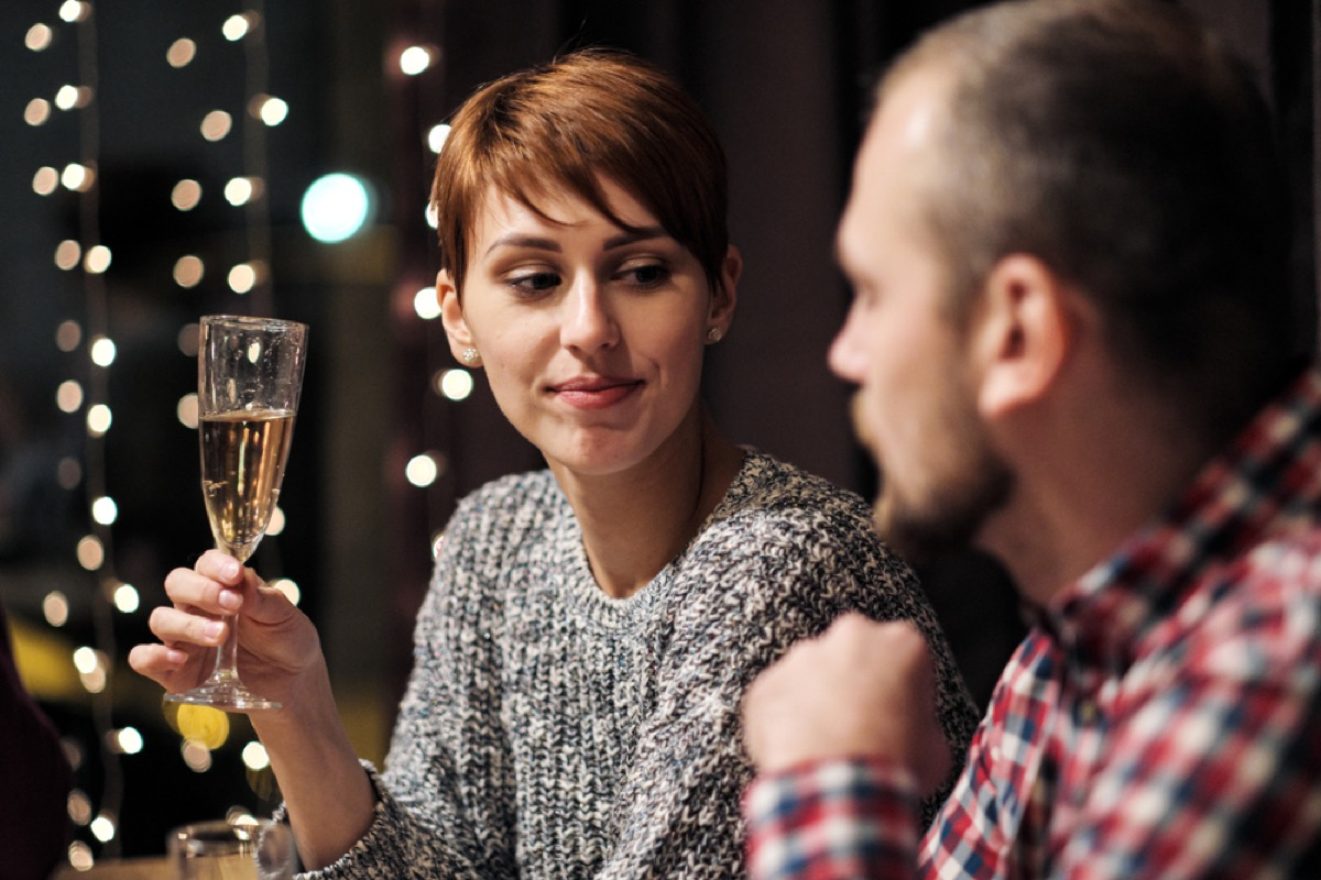 white woman looks annoyed at white man at holiday party