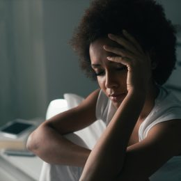 black woman with short hair holding her head and looking tired