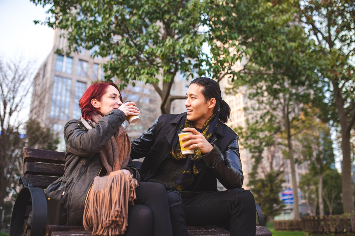 two friends sitting on a park bench drinking coffee